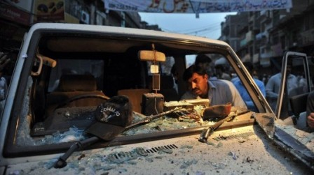 A Pakistani police official examines a damaged police vehicle after a bomb blast in Peshawar. (Reuters)