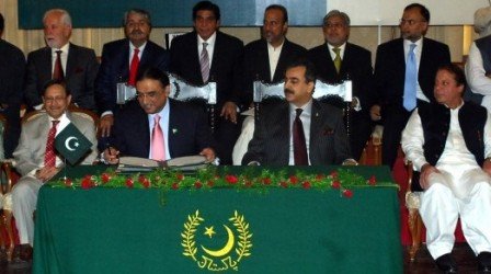 President Asif Ali Zardari signs the 18th amendment into law as Prime Minister Gilani looks on. (AFP)