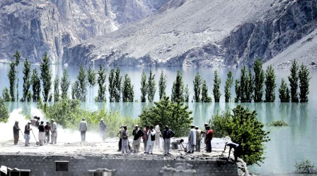 Villagers living near the Attabad lake collect belongings from their homes at Sheeshghat village. (REUTERS)