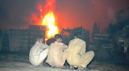 Men sit in front of burnt trucks and tankers in Tarnol late on Tuesday night after unknown attackers set the vehicles on fire. PHOTO: EXPRESS