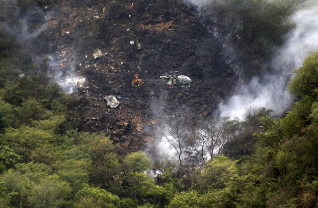 A helicopter flies over the smouldering wreckage of the plane which crashed in the Margalla Hills. PHOTO: REUTERS
