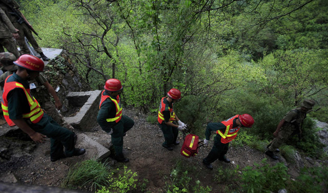 Members of a rescue team make their way through a forested hill towards the wreckage of the plane. PHOTO: REUTERS