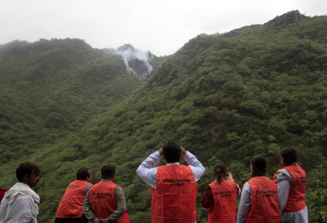 Volunteers on a rescue operation observe as smoke rises from the wreckage of the plane. PHOTO: REUTERS
