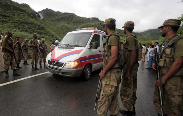 Soldiers stand guard as an ambulance makes its way up a road towards the wreckage. PHOTO: REUTERS