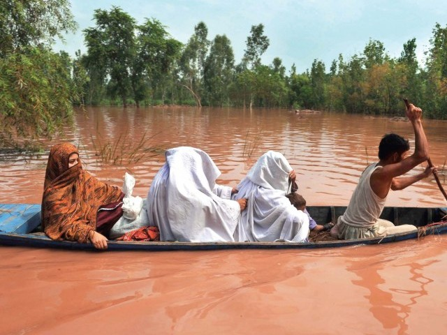 A volunteer uses a small boat to evacuate local residents in a flood-hit area of Nowshera. PHOTO: AFP