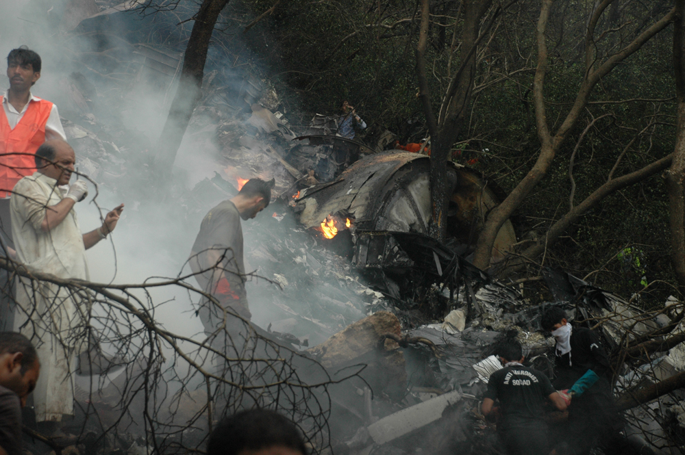 Rescue workers at the site of the crash. PHOTO: QAZI USMAN