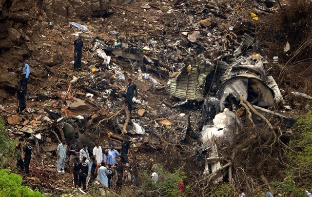 Investigators search for  evidence in the wreckage of the plane. PHOTO: AFP