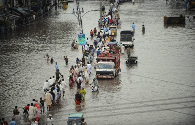 Commuters travel through a flooded street in Lahore. PHOTO: AFP