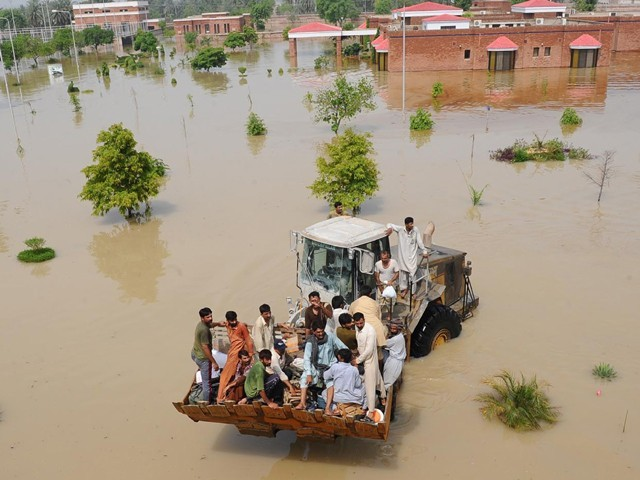 Soldiers use a loader to rescue Lal Pir Thermal Power employees during flooding in Lal Pir on August 7, 2010. PHOTO: AFP