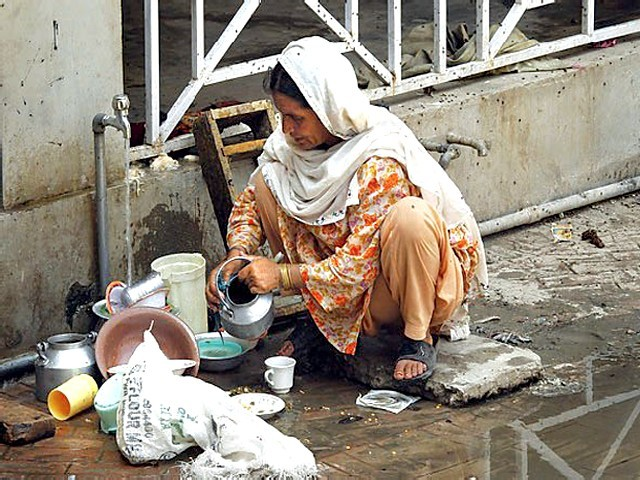 A woman washes dishes on the ground at a hospital providing emergency accommodation for flood victims in Charsadda. PHOTO: REUTERS
