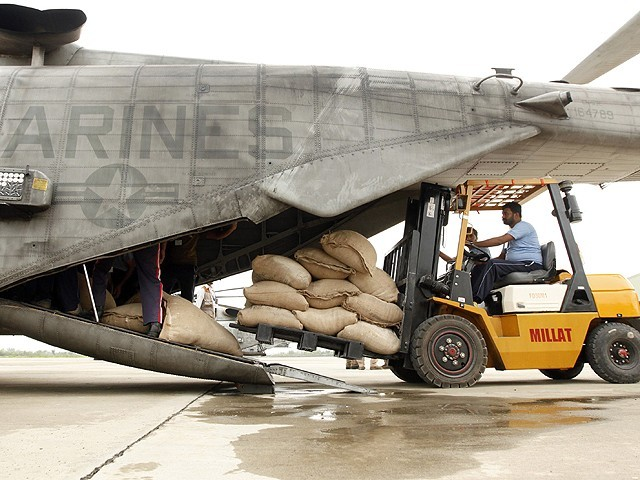 WFP workers load bags of flour for flood victim relief onto a US Marine helicopter. PHOTO: REUTERS