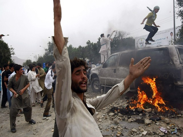A crowd of Afghan protestors destroy a car during clashes with police. PHOTO:REUTERS
