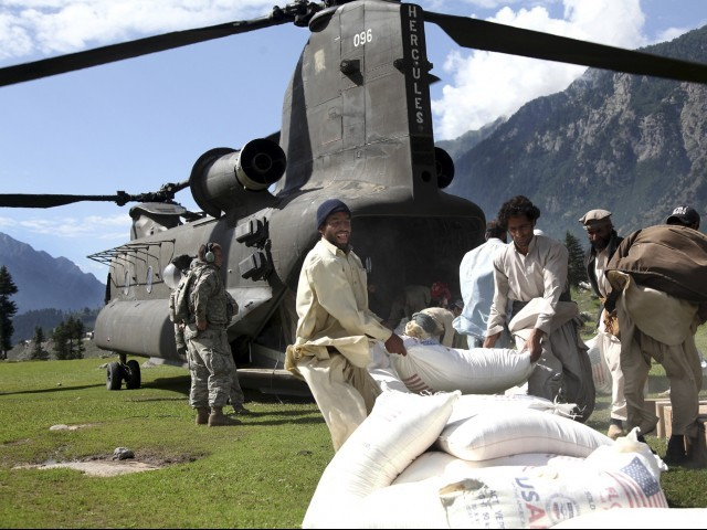 Pakistani men throw a bag of flour onto a pile out the back of a U.S. Army Chinook helicopter that has arrived to deliver humanitarian assistance to flood victims. PHOTO: REUTERS