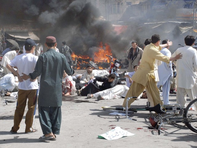 Injured people lie down on the road after an explosion in Quetta on Friday. PHOTO: REUTERS