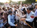 Rights activists clash with police during a protest for the release of Dr. Aafia Siddiqui. PHOTO: EPA