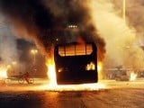 A cyclist rides past a burning passenger bus torched by angry mob during a protest in Karachi. PHOTO: AFP
