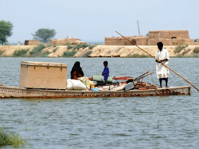 A Pakistani flood affected family rides on a boat as they evacuate their village. PHOTO: AFP