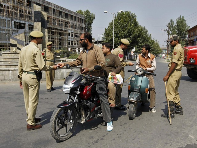 Indian police check the identity cards of Kashmiri motorists at a checkpoint during a curfew in Srinagar. PHOTO: REUTERS
