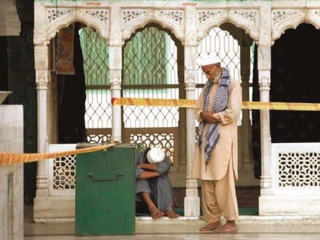 A devotee prays while another mourns inside the shrine just hours after the blast. PHOTO: REUTERS