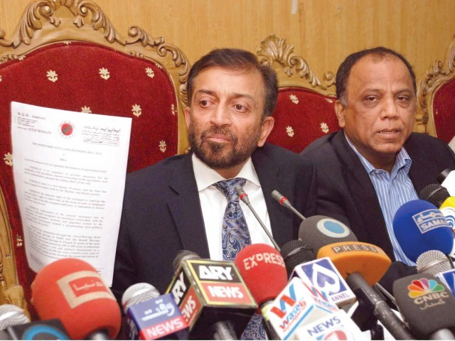 MQM leader Dr Farooq Sattar holds a copy of the 'Redistributive Land Reforms Bill 2011' in Islamabad. PHOTO:PPI