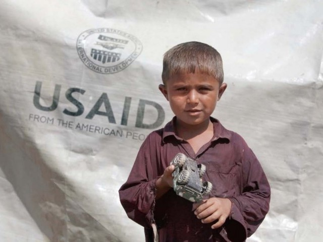 Sajad, 7, who has been displaced by flooding, holds his toy jeep outside his family tent with a weather sheet, while taking refuge on an embankment near Dadu. PHOTO: REUTERS