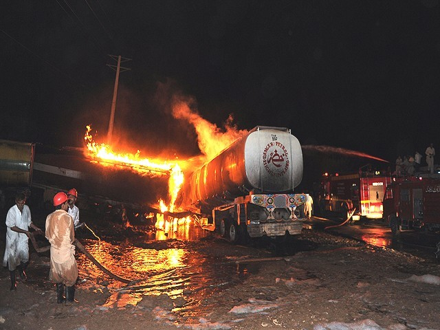 Pakistani firefighters try to extinguish burning Nato supplies oil tankers following the gunmen attack on the outside of Islamabad on October 4, 2010. PHOTO: AFP