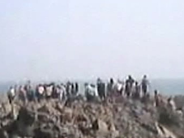 Screenshot shows people who climbed atop the piece of land that surfaced from the sea.