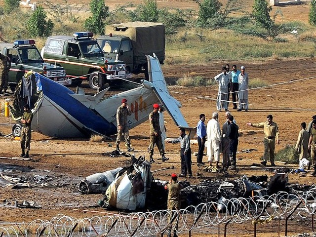 Rescuers and airport security personnel gather at aircraft crash site in Karachi on November 5, 2010. PHOTO: AFP