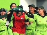 Pakistan players run with the national flag to celebrate their victory over Bangladesh in the women's limited overs cricket gold medal final at the 16th Asian Games in Guangzhou on November 19, 2010. PHOTO: AFP