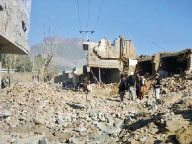 Locals stand on the debris of the hospital a day after an attack on the building in Hangu district. PHOTO: AFP