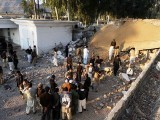 Security personnel are seen gathered at the suicide attack site in the district of Mohmand, on December 6, 2010. PHOTO: AFP