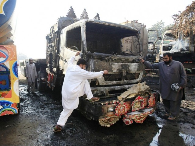 File photo shows men surveying a damaged oil tanker, used for supplying fuel for NATO forces in Afghanistan, after they were attacked in the outskirts of Peshawar November 20, 2010. PHOTO: REUTERS/FILE