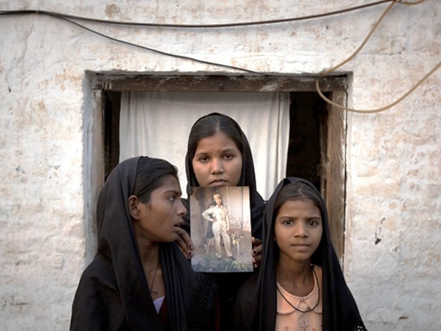 The daughters of Aasia Bibi with an image of their mother, standing outside their residence in Sheikhupura on November 13, 2010. PHOTO: REUTERS