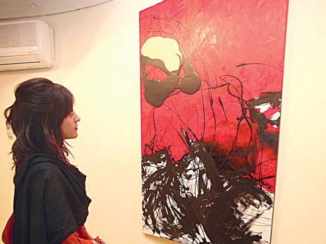 A visitor views paintings by Sonia Chundrigar at Khaas Art Gallery on Tuesday. PHOTO: MUHAMMAD JAVAID