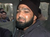 Arrested sits in a police van at the site of a fatal attack on Salman Taseer, the governor of Punjab, by his bodyguard in Islamabad on January 4, 2011. PHOTO: AFP