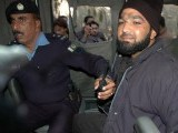 Arrested suspect sits in a police van at the site of a fatal attack on Salman Taseer, the governor of Punjab, by his bodyguard in Islamabad. PHOTO: AFP