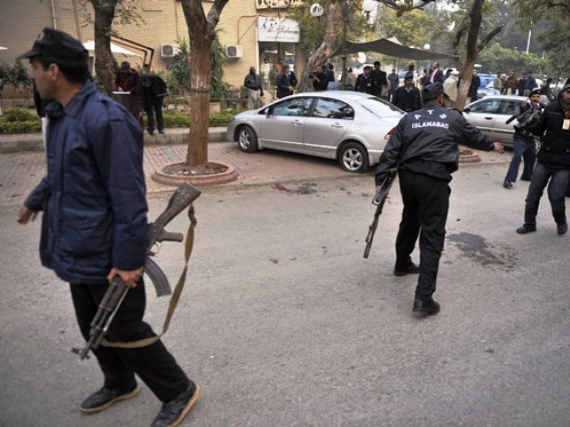 Policemen secure the site of a fatal attack on Salmaan Taseer, the governor of Punjab, by his bodyguard in Islamabad on January 4, 2011. PHOTO: AFP