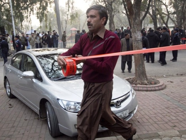 A plain-clothed policeman cordons off the site where the governor of Punjab province Salmaan Taseer was shot dead. PHOTO: REUTERS