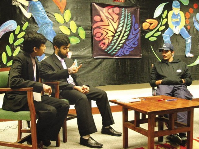 : (From left to right) Students Muhammad Salman Khalil and Muhammad Abdullah Ali take part in the Anchor IT competition along with a volunteer impersonating Younus Khan. PHOTO: COURTESY LUMS CARMA