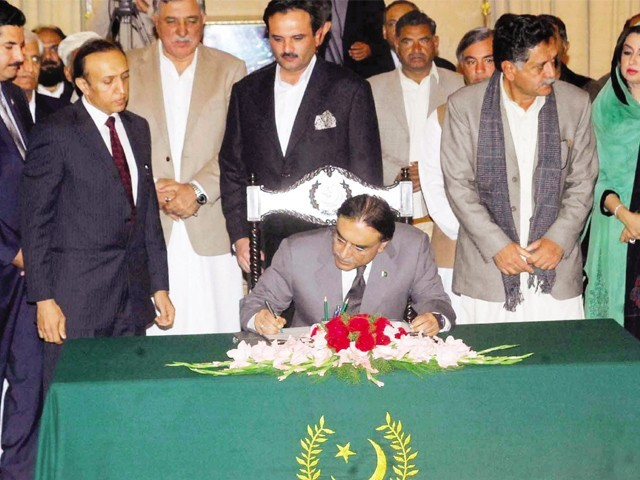 President Asif Ali Zardari signs a document changing the status of Kala Dhaka in Khyber-Pakhtunkhwa from a Provincially Administered Tribal Area (PATA) to that of a settled area at the President House in Islamabad. PHOTO: INP