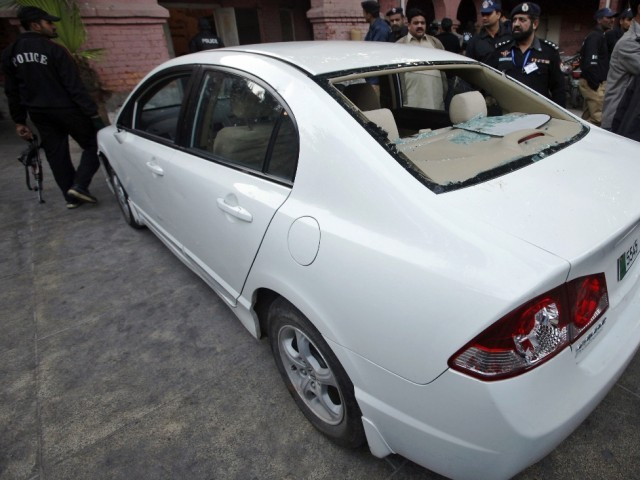 Policemen stand next to a car, which police said a U.S consulate employee was travelling in when he was engaged in a shoot-out, after it was brought to a police station in Lahore. PHOTO: REUTERS/FILE