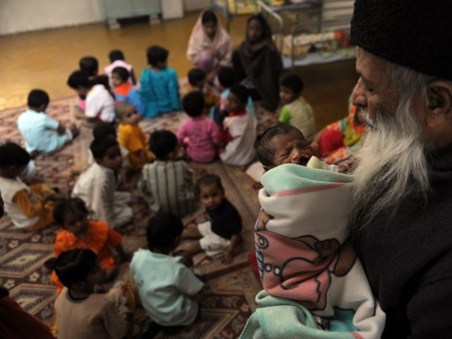 In this photograph taken on December 6, 2010 Abdul Sattar Edhi, head of Pakistani's Edhi foundation holds a disabled orphan at the orphanage of the charity in Karachi. PHOTO: AFP