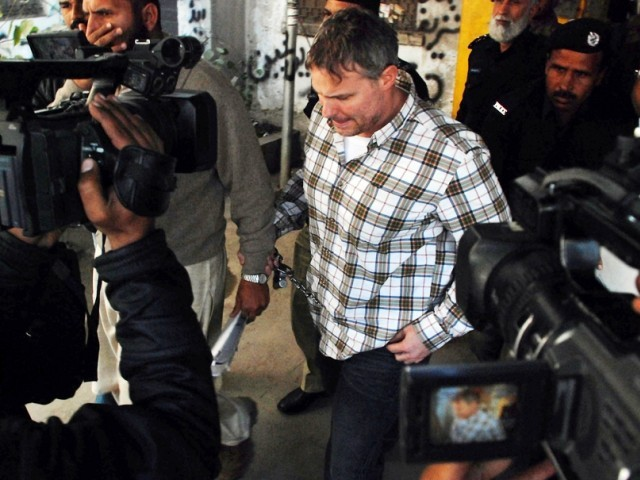 US consulate employee Davis is escorted by police and officials after appearing before a judge in Lahore. PHOTO: AFP
