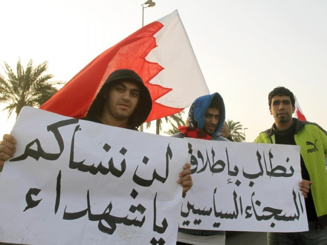 "Bahraini protesters holds signs in Arabic that read, ""We will not forget you oh martyrs"" (L) and ""We demand the release of political prisoners"" (R) as they gather in Pearl Square (roundabout) in the capital Manama, on February 16, 2011. PHOTO: AFP"