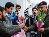 A Pakistani policeman receives flowers and cards from students for detained self-confessed killer Malik Mumtaz Hussain Qadri outside the Adiyala prison in Rawalpindi on February 14, 2011. PHOTO: AFP