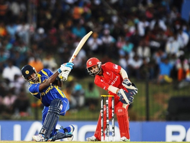 Sri Lankan cricketer Angelo Mathews (L) is watched by Canadian wicketkeeper Ashish Bagai (R) as he plays a shot during the Group A match in the World Cup Cricket tournament. PHOTO: AFP