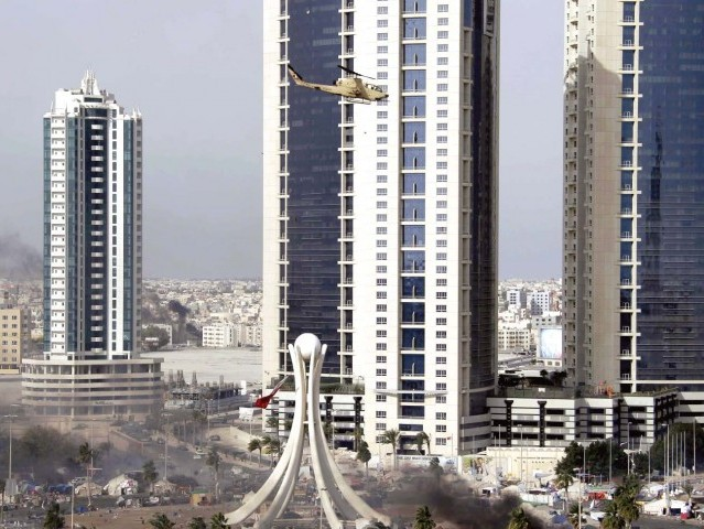 An army helicopter hovers over Pearl Square in the Bahraini capital Manama as heavily armed police forces raid a month-old pro-democracy sit-in. PHOTO: AFP