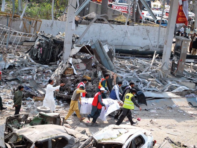 Rescue workers remove the body of a victim at the bomb blast site in Faisalabad. A bomb planted by suspected militants exploded at a filling station, killing at least 25 people and wounding 130 others. PHOTO: AFP