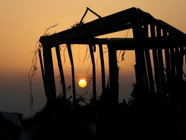 The skelton of a house, which was damaged by a tsunami, stands in the orange sky of sunset at Higashimatsushima city in Miyagi prefecture on March 19, 2011. PHOTO: AFP