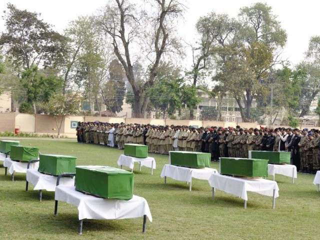 Officers and personnel of security forces offer prayers for their colleagues during their funeral in Peshawar. PHOTO: AFP